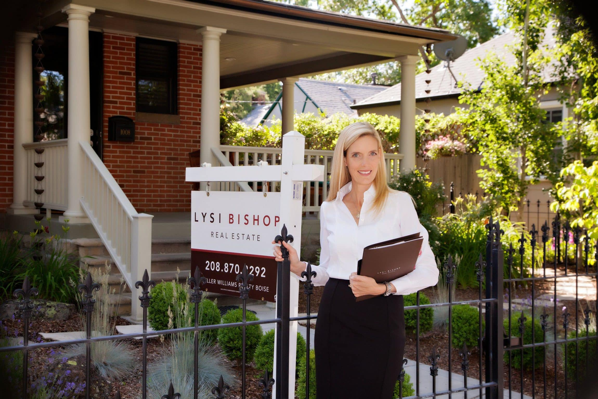 Woman standing in front of a house for sale