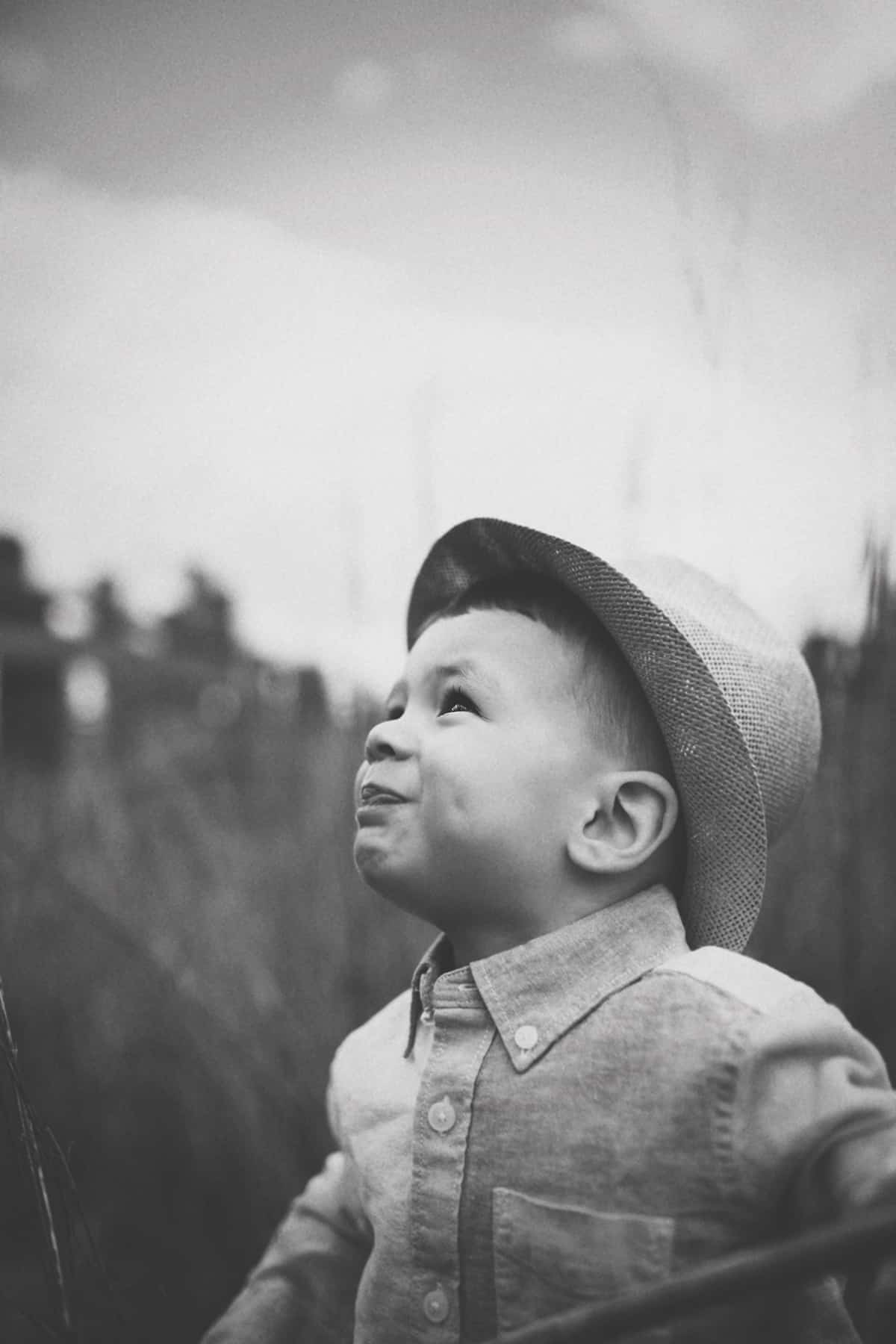 Child looking up wearing a hat