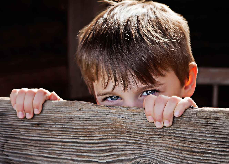 Child peeking over a piece of wood