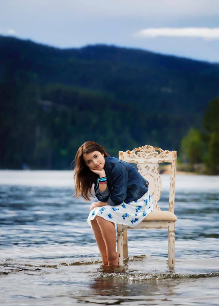Child sitting in a chair on a beach shore