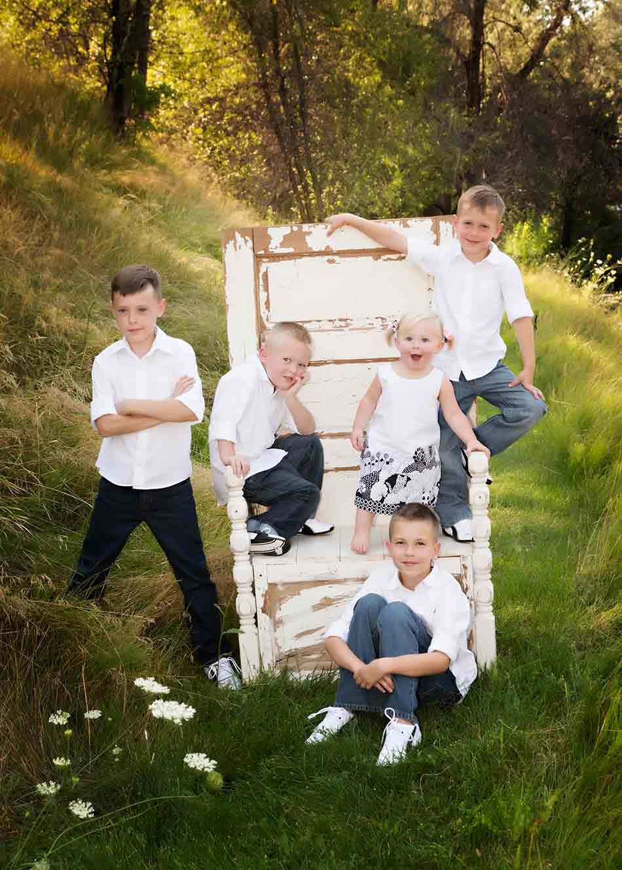 5 children on and around an antique chair