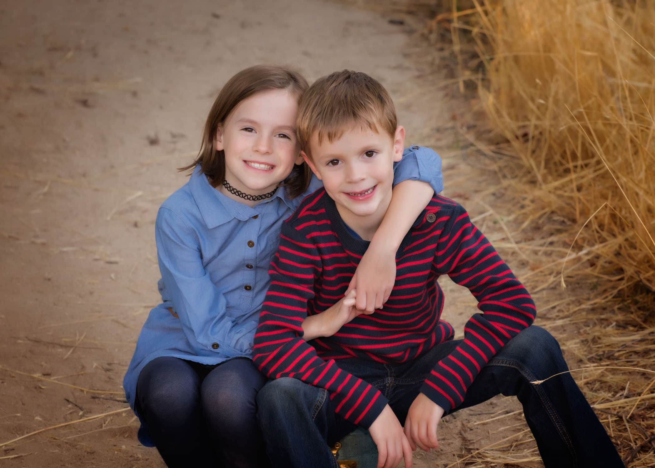 2 children sitting on a dirt road