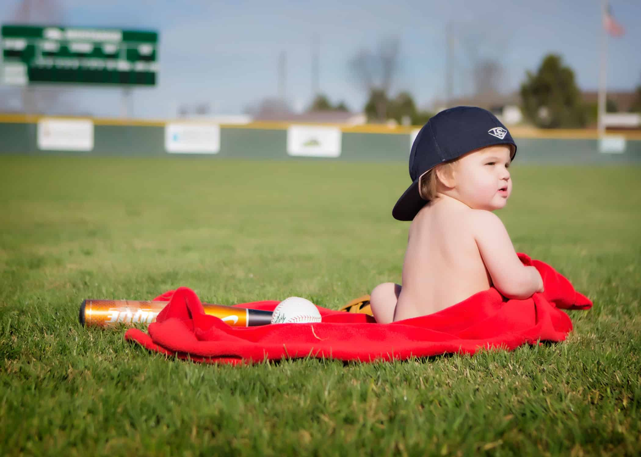 Baby sitting on red blanket with a baseball and bat.