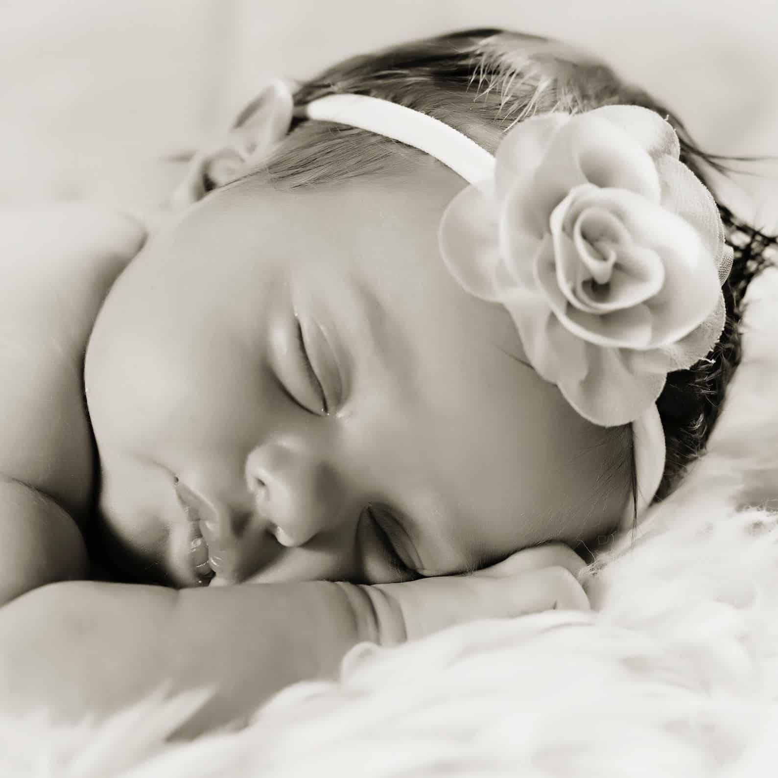 Baby lying down with a flower headband