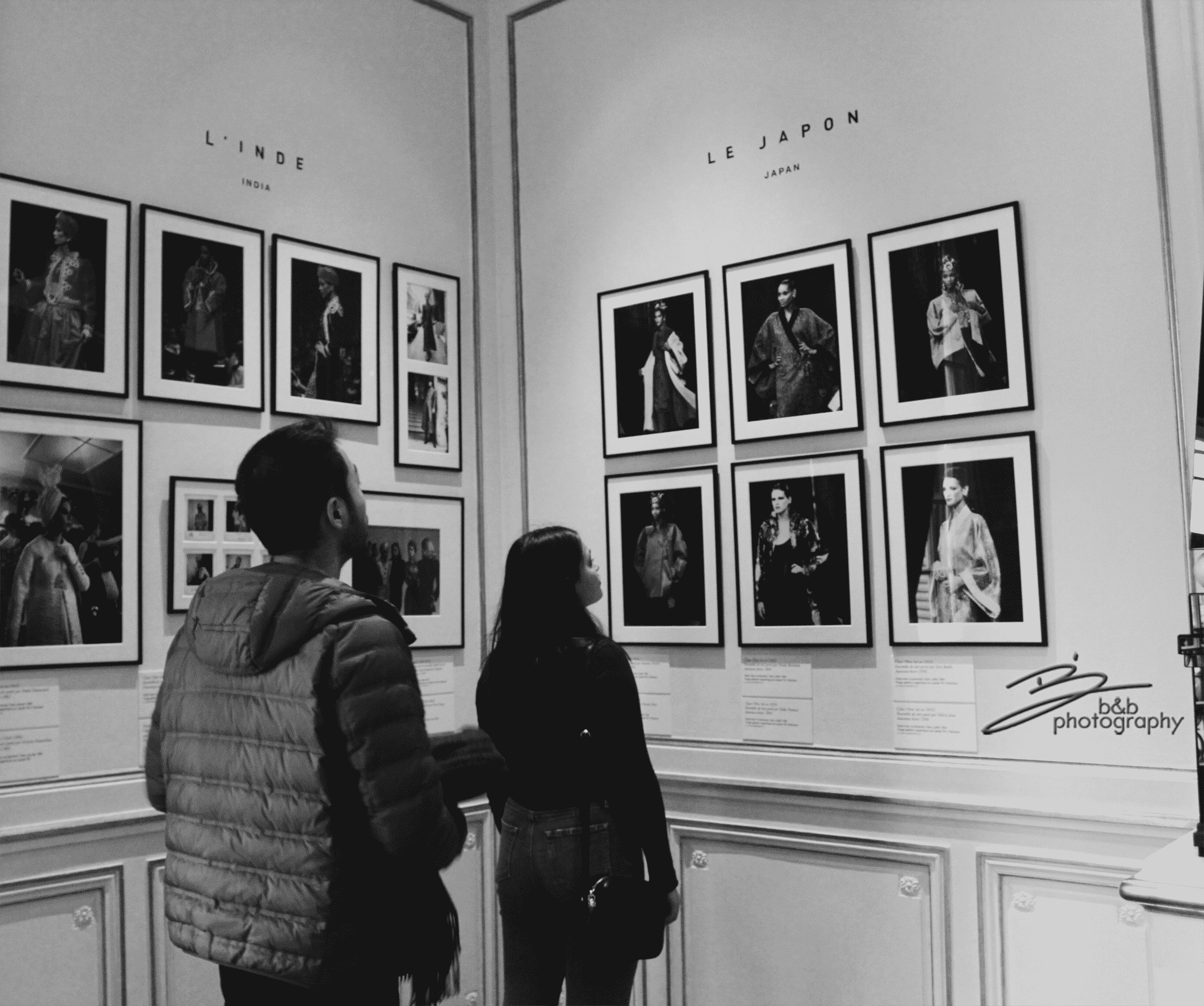 A black and White image of people staring at photos in a gallery