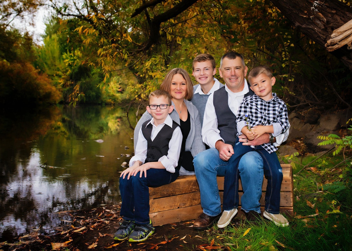 Family sitting on a bench on a river bank.