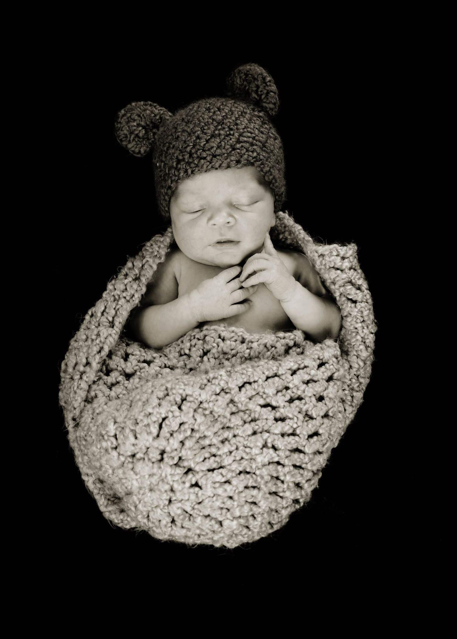 newborn in knitted blanket