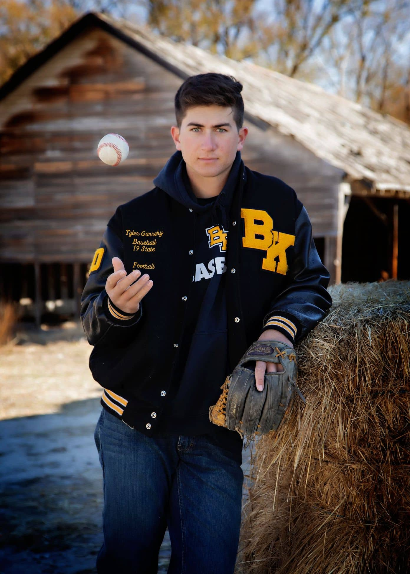 Man leaning against hay holding a baseball glove and ball.