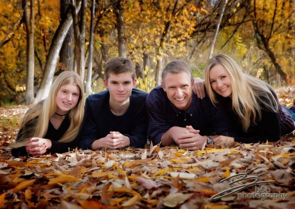 Family posing outside while laying in leaves