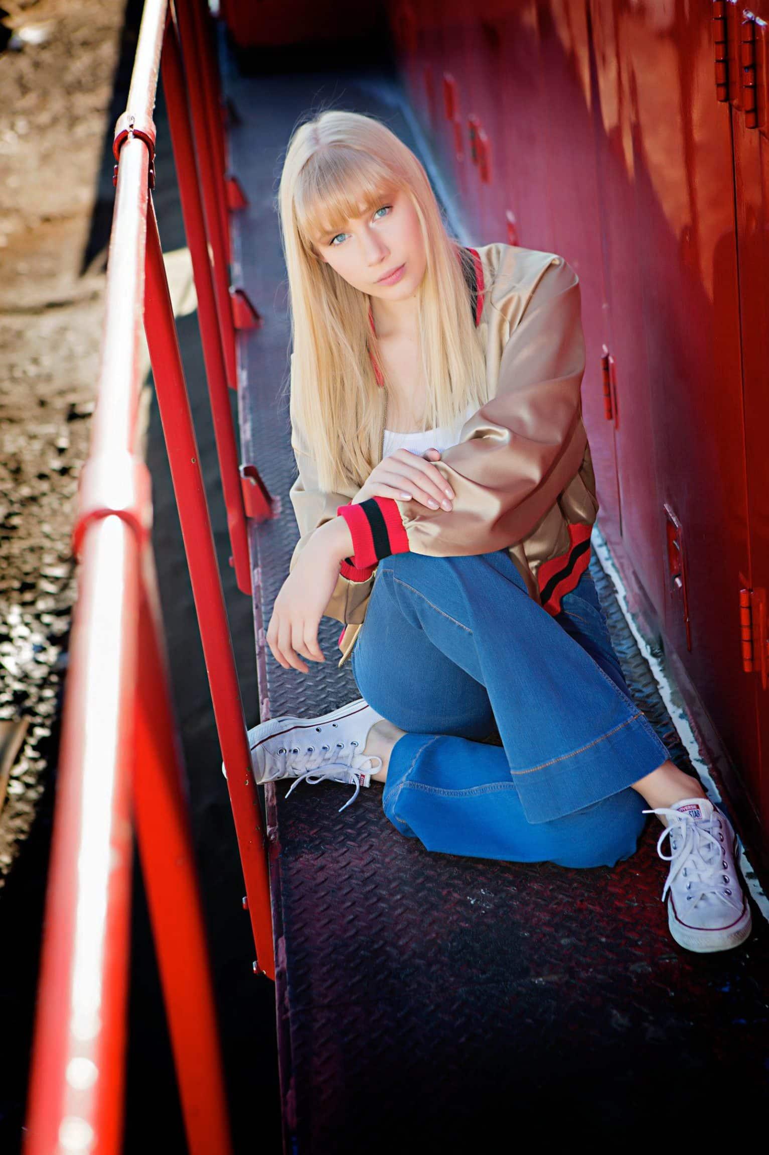 Woman sitting between railing and lockers