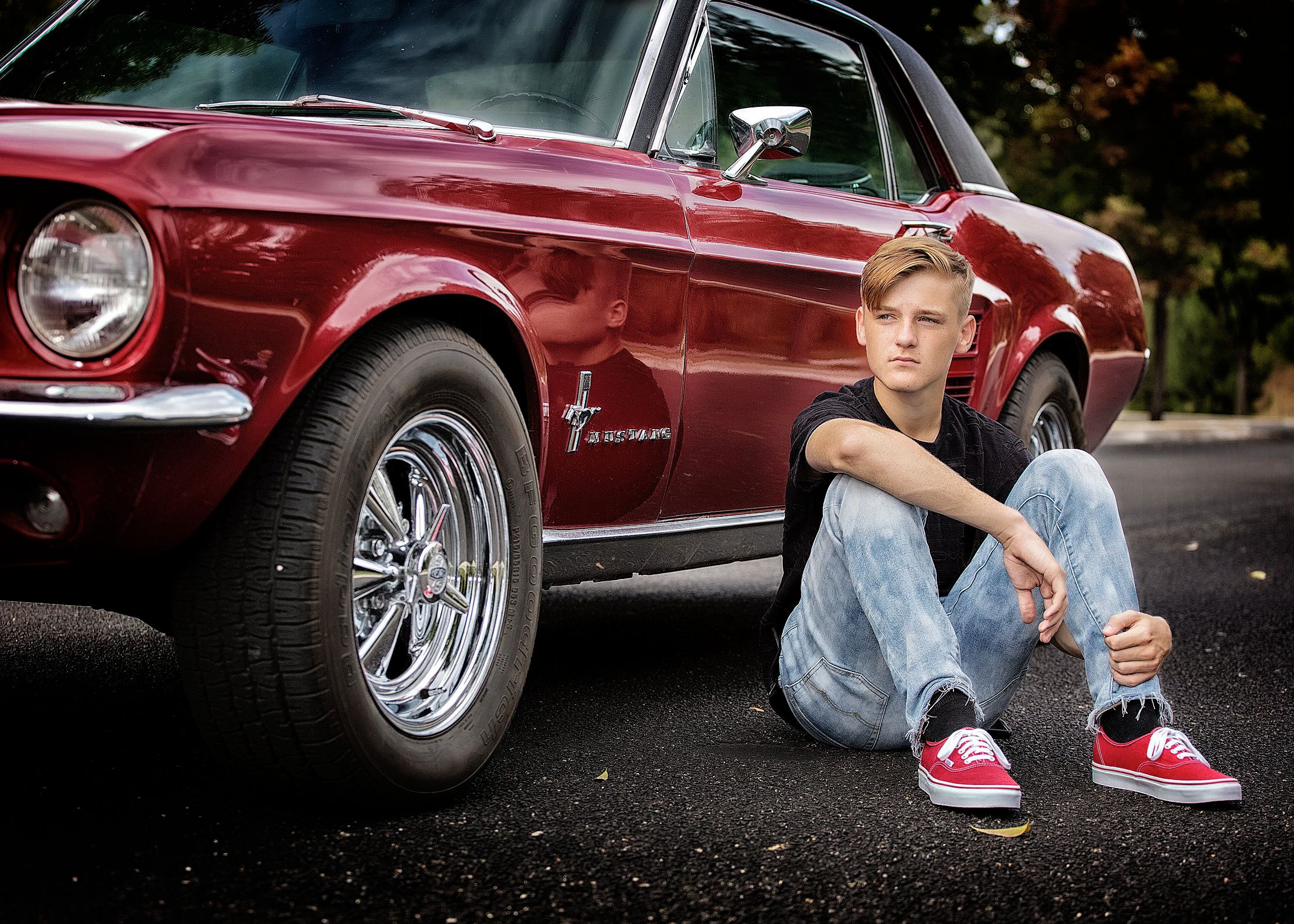 Teen sitting next to an old sports car