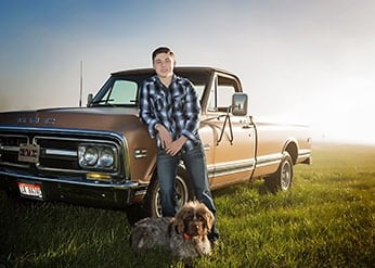 Man leaning against truck with a dog at his feet.