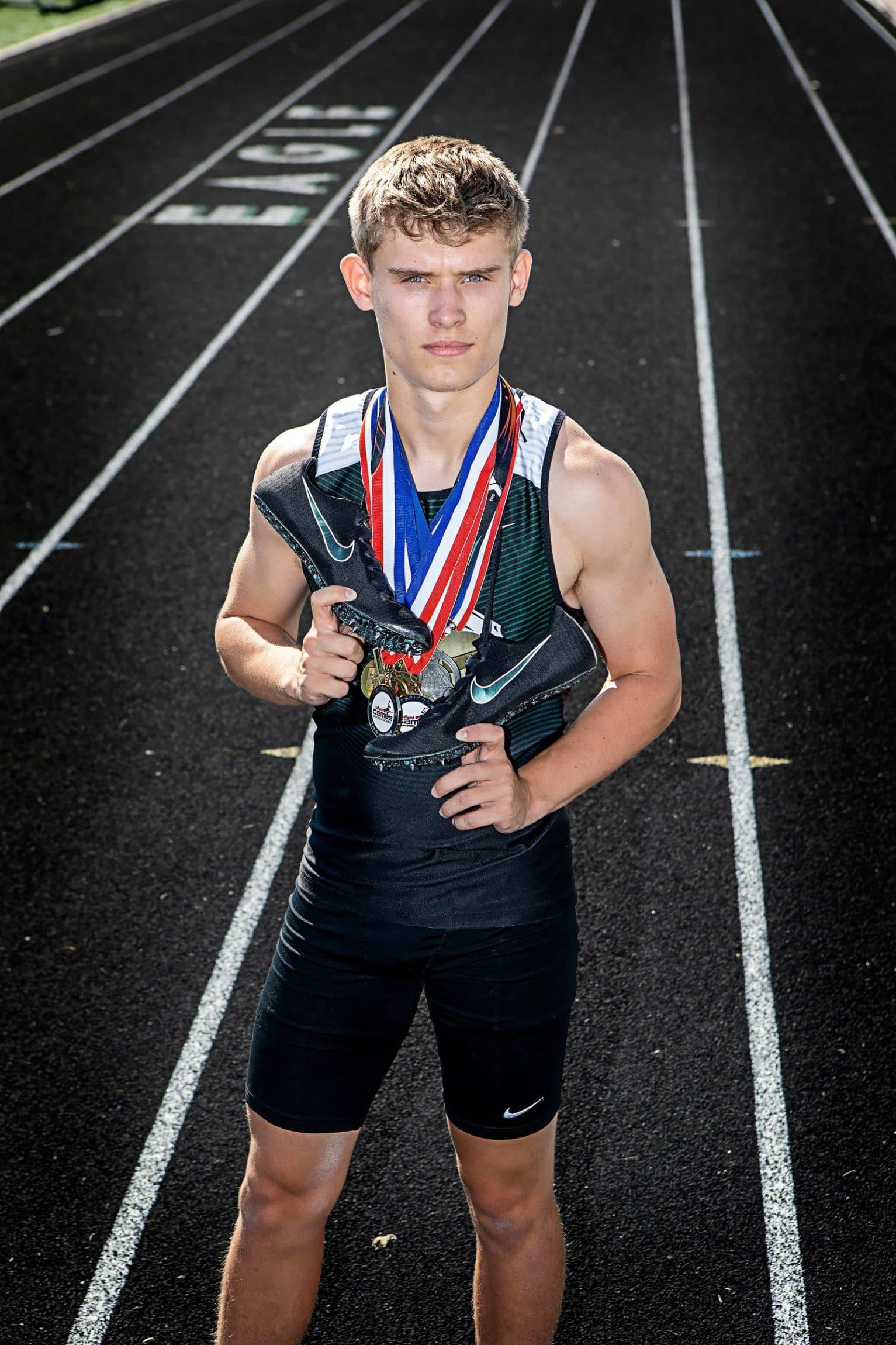 Man with medals holding shoes standing on a track.