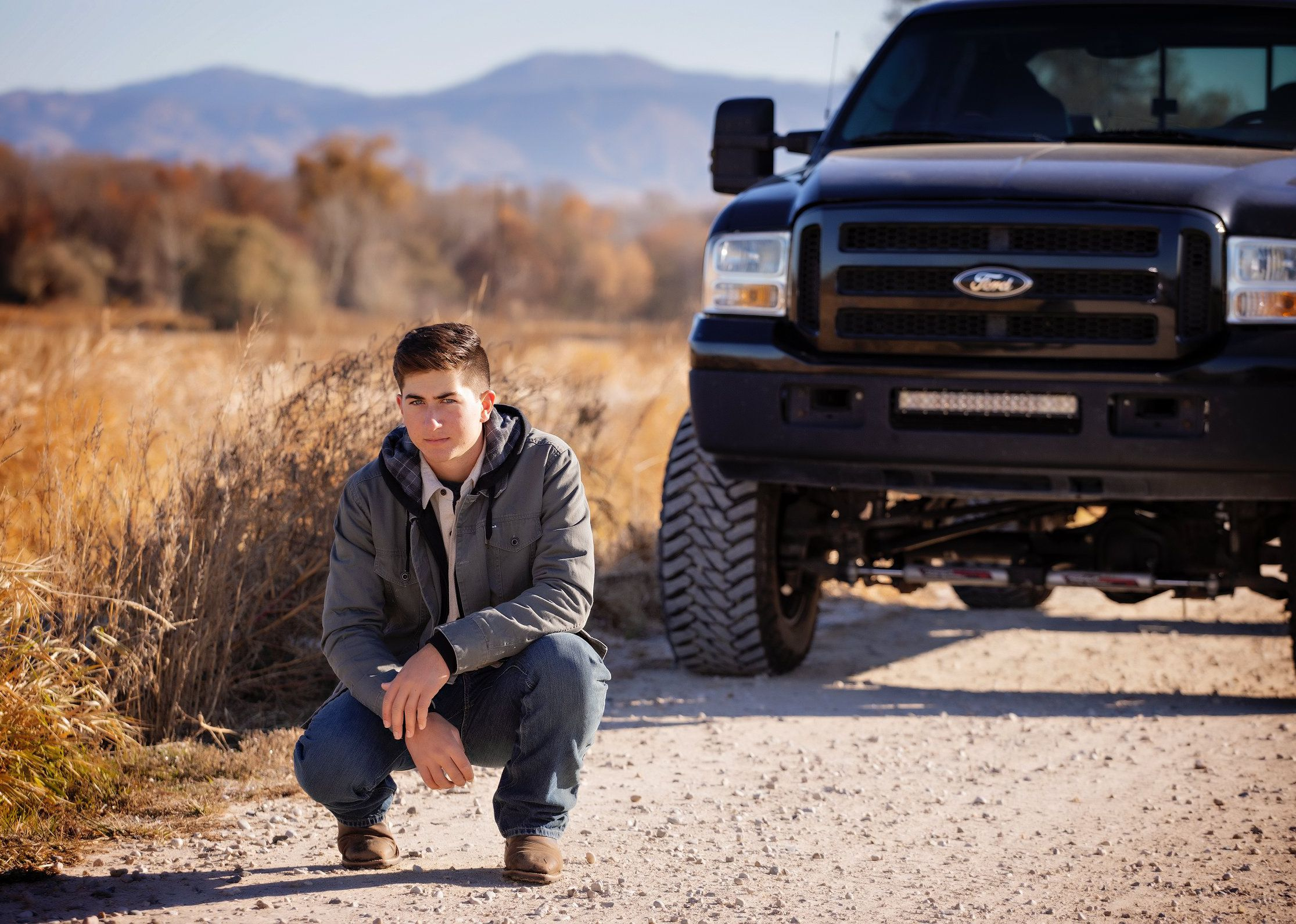 Man crouching in front of a truck