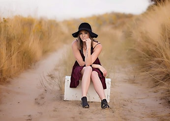 Woman sitting on a box on a dirt road.