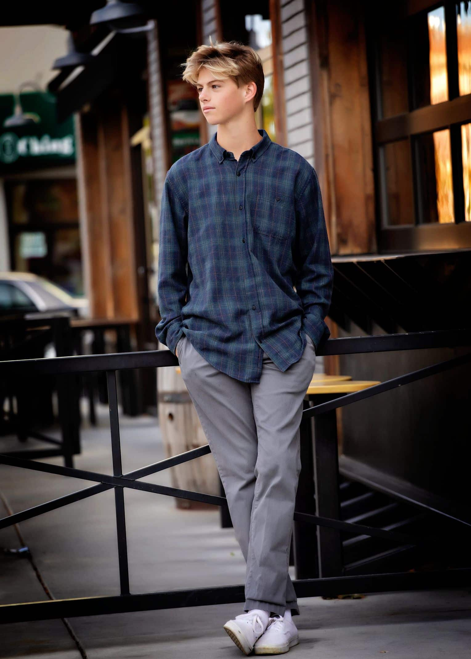 Teen leaning against storefront rail