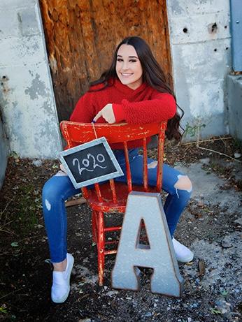 "Woman sitting backwards in a char with a chalkboard that has ""2020"" written on it."