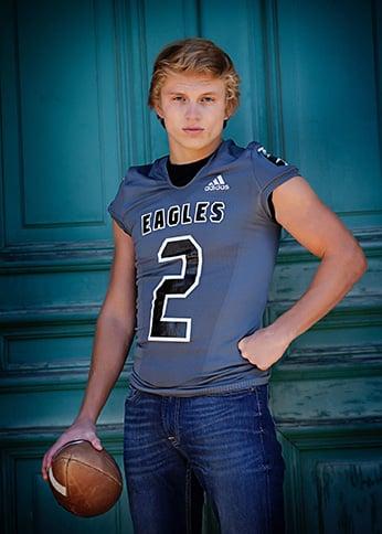 Teen wearing jersey holding football