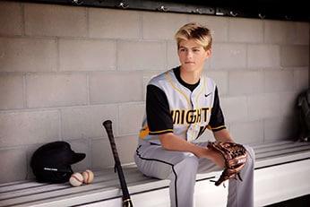 Teen sitting on bench next to baseball bat