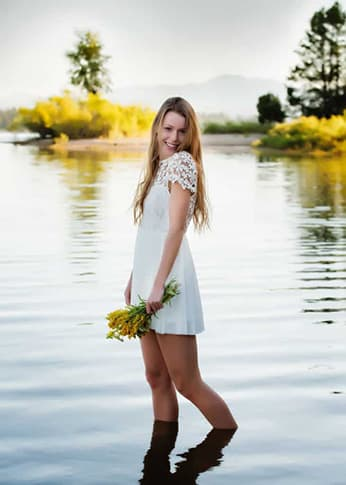 Woman standing in water holding flowers