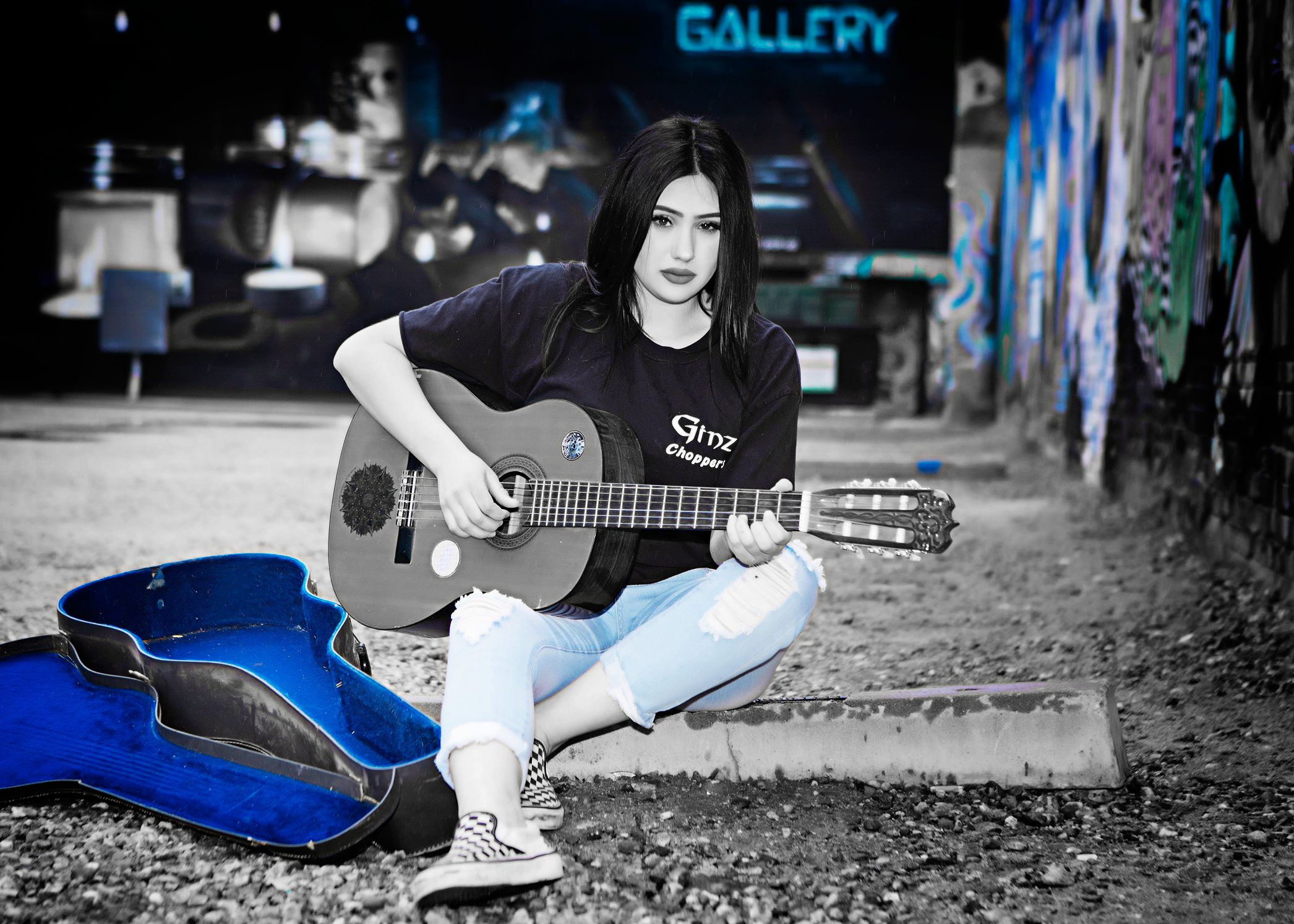 Woman sitting on concrete playing a guitar