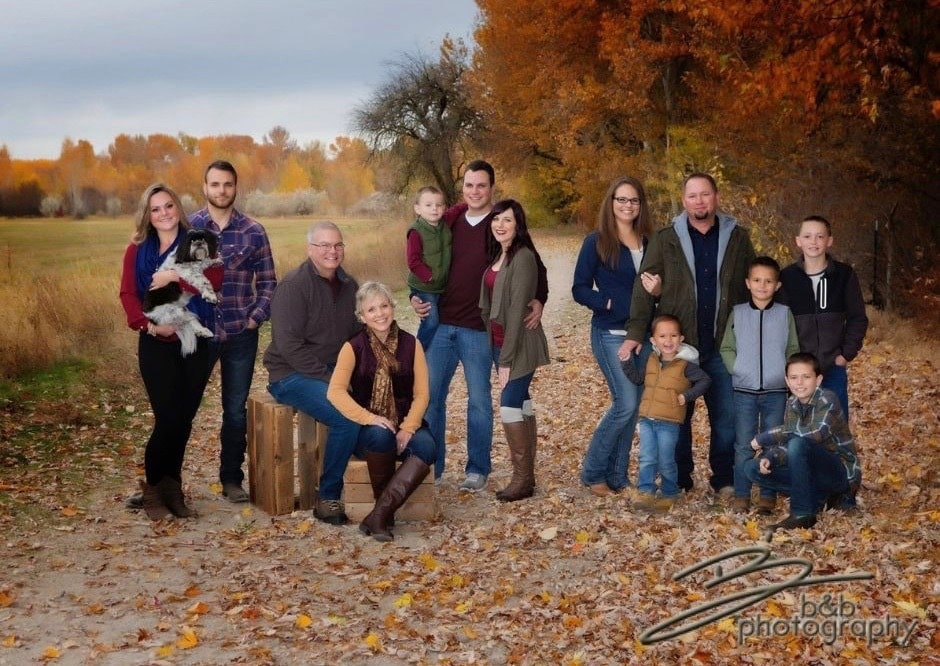 Extended family pictured together with children and a beautiful fall backdrop.
