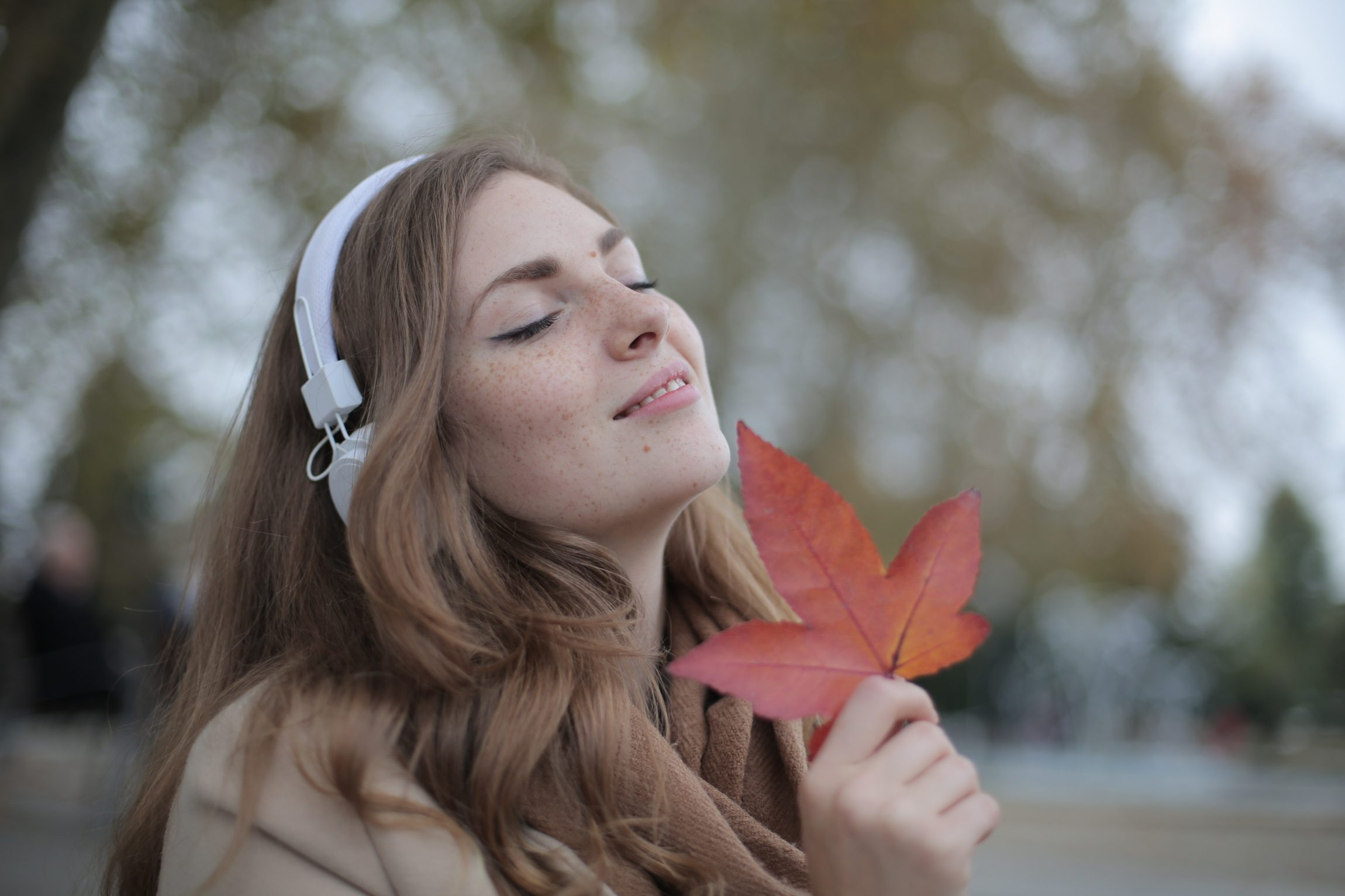 College woman with headphones on and eyes closed smelling a leaf