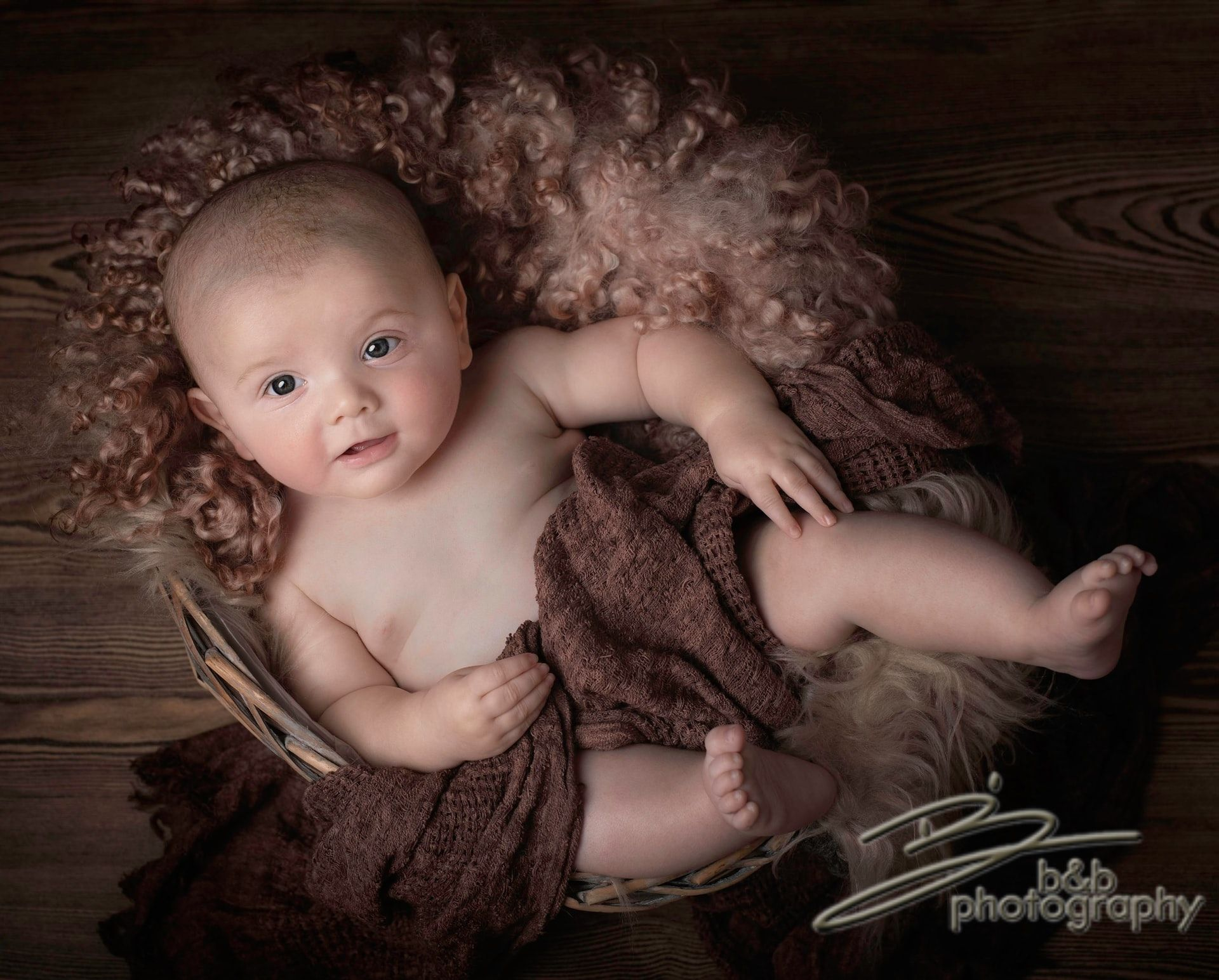 Baby in a basket with a brown blanket